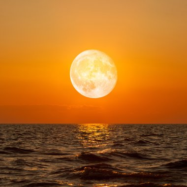 Full moon rising over empty ocean