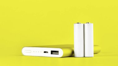 Portable yellow power bank for charging mobile devices and AA batteries.