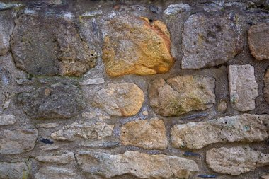 A stony wall of natural -or sandstone as background or texture