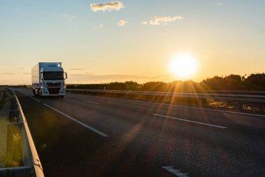 Dondurulmuş yarı römorklu bir kamyon, akşam üstü güneş batarken otoyolda gidiyor..