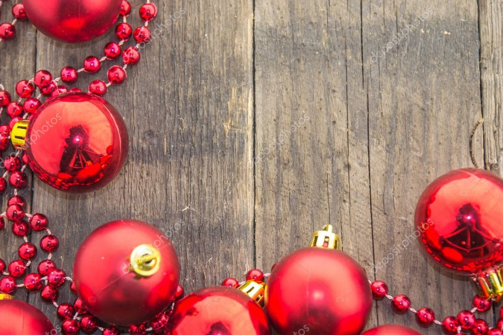 Christmas decoration with shiny red balls and red beads on a wooden base