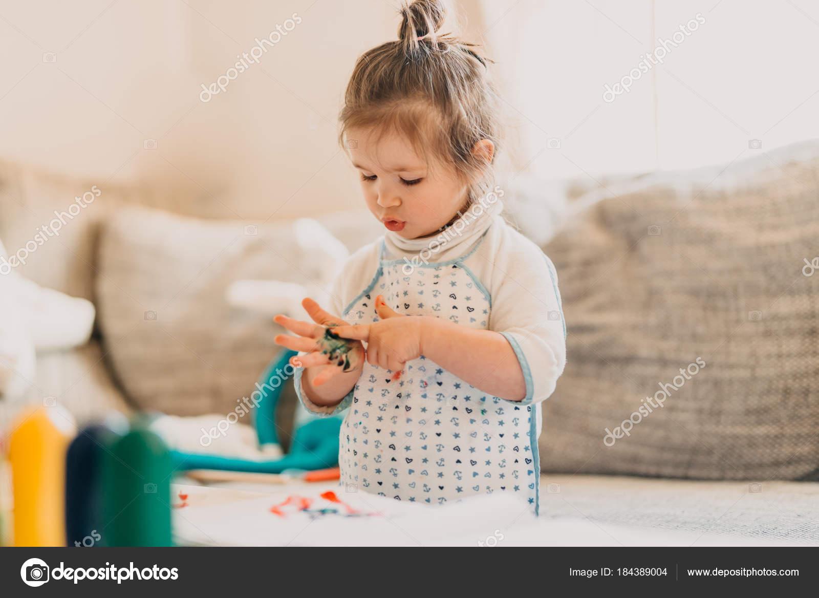 Kleinkind Mädchen Auf Der Zeichnung Schürze Zieht Finger Zu Hause
