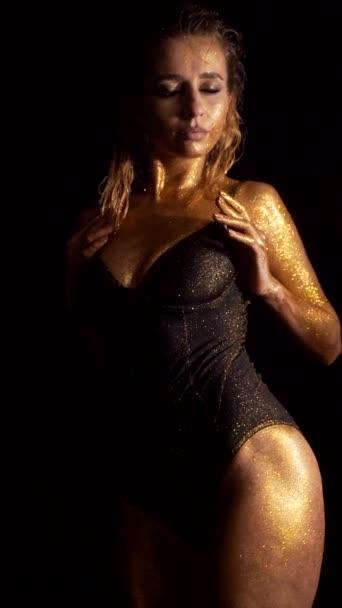 dívka se zlatou pletí na černém pozadí. Sexy žena ve spodním prádle zvedne ruce a pohladí se po těle erotické pózování na kameru. svislý rámec