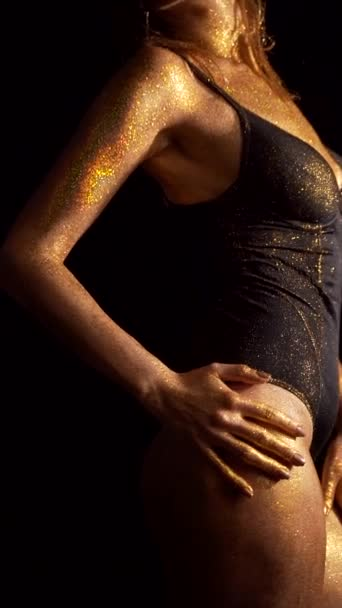 Girl body with golden skin on black background. sexy woman in lingerie hands sexually stroking body.vertical frame