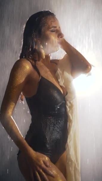Vzrušená sexy žena v černém prádle hladí její tělo pod vodou. Nahá dívka se zlatou pletí tančící ve sprše na tmavém pozadí. Po těle stékaly kapky vody. Svislý rámec