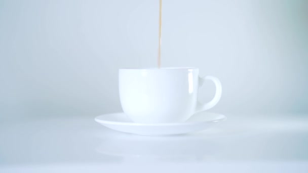 pour coffee into a white cup. white background. side view