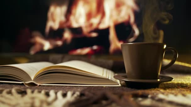 Hygge concept with open book and cup of coffee near burning fireplace. Coffee mood. Background. relax time. 4K