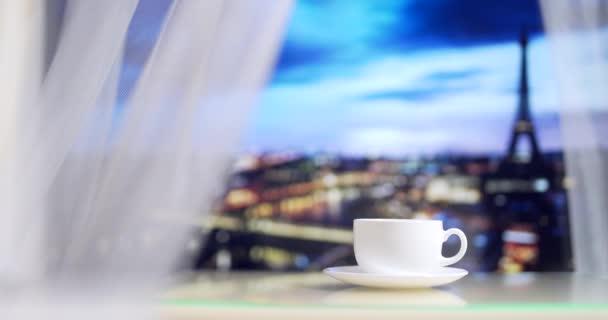 Eiffelova věž z hotelového okna. Káva na bílém stole na večerním pařížském pozadí. Jeď do Paříže. Líbánky. Restaurace poblíž Eiffelovy věže. S detailem. 4K