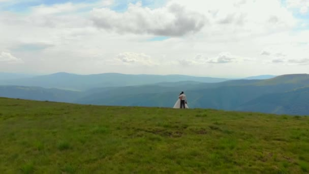 young wedding couple walking on top of green mountains. Against the backdrop of a mountain in love young people in wedding clothes. Aerial view. Mountain meadow and green grass