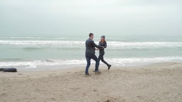 Milující pár Bavit Běh Podél Winter Beach Společně. kluk a holka zrzka. v černém. studený déšť, usmívající se ruce, skákání. pobřeží moře nebo oceánu. vlny. Zpomal. příběh