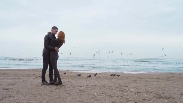 young loving couple standing kissing by the sea.  coast on a background of sea landscape.  winter or autumn wind cold weather rain, lovers dancing hugging, smiling at each other.  walking along birds