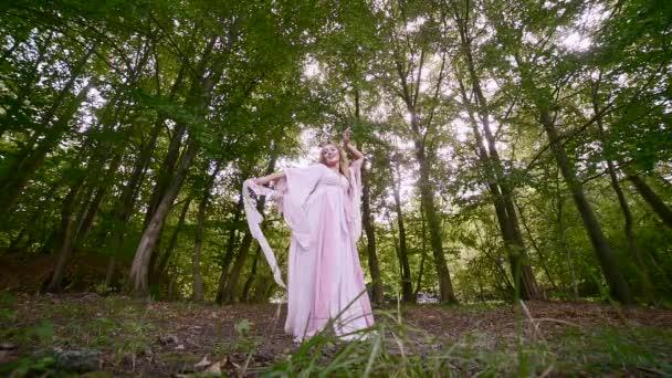 fiatal elegáns lány egy hosszú rózsaszín ruhában táncol az erdőben. fák között, lassított felvétel. vonzó szőke, gyönyörű természetben. Luxus nő. Szexi tündér. boldog divat modell szőke haj