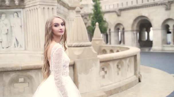 portrét mladé atraktivní luxusní módní dívky, nevěsta kráčející po náměstí starého hradu, dlouhé blond vlasy, nahá záda, bílé svatební šaty, víla princezna v zámku. zpomalit. za.