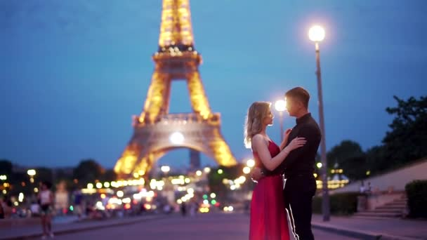 young attractive girl in a red dress fits to a guy in black clothes, against the background of evening Paris and the Eiffel Tower. Blurred background, bokeh from old city lights. slow motion