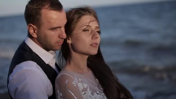 Portrait of close up, charming exquisite young couple. in wedding dress. Stylish luxury serious bride and groom, two faces background. man touches hair. kisses on the shoulder sniffs. Romantic eyes