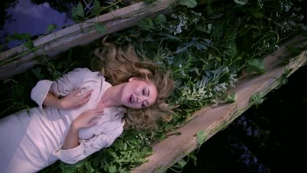Hezká žena leží na lodi, která je zdobena bílými květy, bylinkami. Šípková Růženka ve starých šatech s vlakem plave Portrét blond zpěvu v přírodě. Říční nymfa. Pohádková princezna