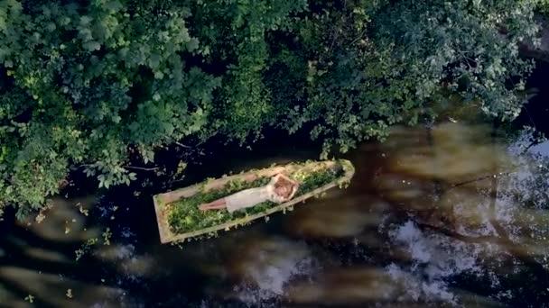 Mladá tajemná žena s dlouhými blond vlasy leží a vznáší se v dřevěné lodi. zdobené květinami, bylinkami. přírodní lněné šaty. Horní letecký pohled. tropická řeka. relaxovat a meditovat zelené listy