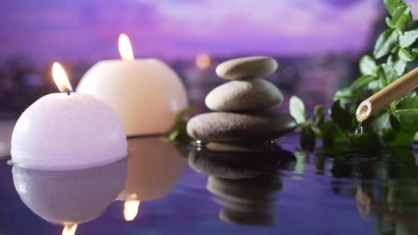 Spa Still Life, masáže kamenů a vodní relax. Zavřít. Uvolňující pohled na hořící svíčky. odraz vody na rozmazaném pozadí. Relaxace, klid, meditace, klid a pohoda v přírodě