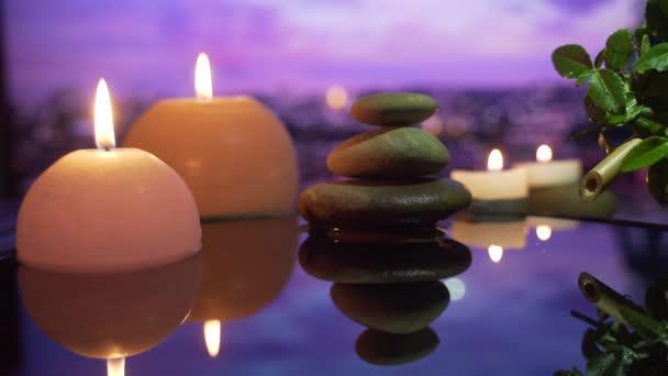 Spa Still Life, masáže kamenů a vodní relax. Zavřít. Uvolňující pohled na hořící svíčky. odraz vody na rozmazaném pozadí. Relaxace, meditace, klid a ticho.