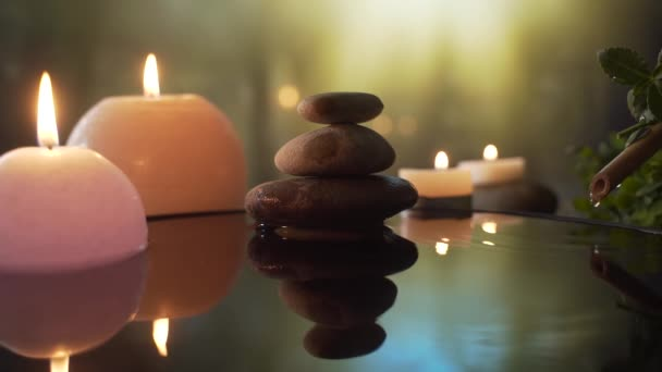 hořící svíčky ve vodě, odraz kamení na pozadí večerní přírody, kapky vody padající. zpomalit. Close up Koncept: relaxace, wellness, péče o tělo, lázně, aromaterapie