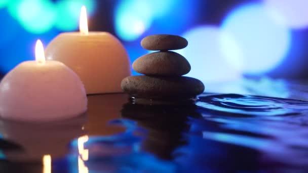 hořící svíčky ve vodě, odraz kamenů na abstraktním modrém pozadí, kapky vody padající. zpomalit. Zavřít. Koncept: relaxace, wellness, péče o tělo, lázně, příroda, aromaterapie a vůně