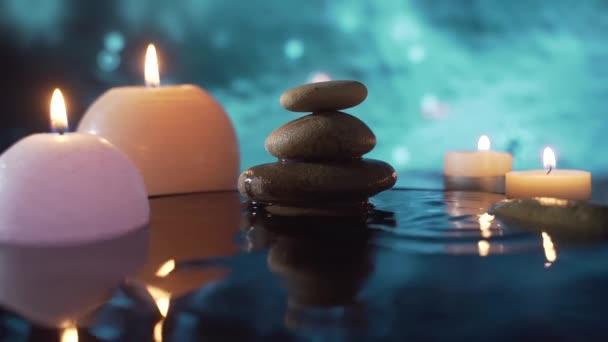 Spa Csendélet, Kövmasszázs és Vízellazulás. Közelről. Pihentető látvány az égő gyertyákról. víz elmosódott háttér tükröződése. Pihenés, nyugalom, meditáció, béke és nyugalom a természetben