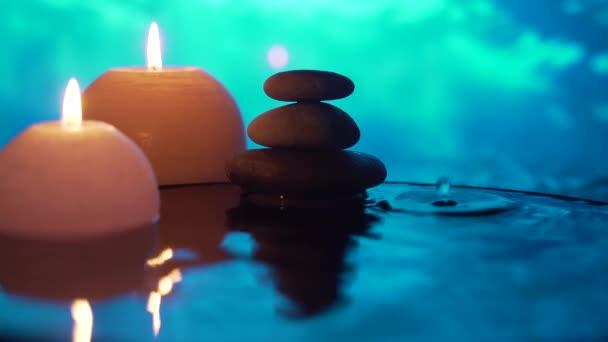 Spa Stillleben, Stones Massage und Water Relax. Aus nächster Nähe. Entspannender Blick auf brennende Kerzen. Wasserspiegelung auf verschwommenem Hintergrund. Entspannung, Ruhe, Meditation, Ruhe in der Natur