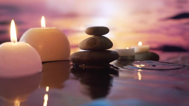 burning candles in the water, the reflection of stones on the background of evening nature, water drops falling. slow motion. Close up Concept: relaxation, wellness, body care, spa, aromatherapy