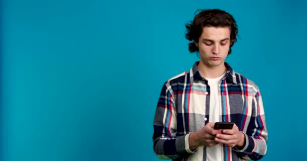 Pensive young man typing on smartphone and looking away isolated on blue background