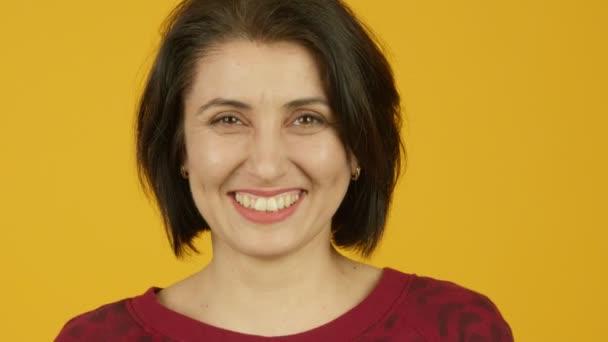 Přední pohled šťastné ženy středního věku smějící se na kameru