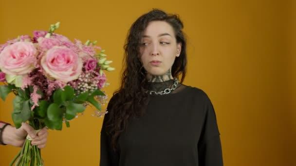 Tetovált lány elfogadja a virágokat és csukott szemmel mosolyog