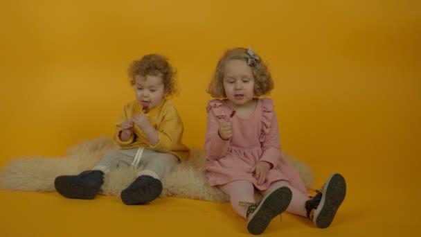 Dvě kudrnaté děti sedící na koberci a pojídající lízátka