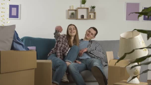 Smiling couple embracing on sofa and looking at cardboard boxes