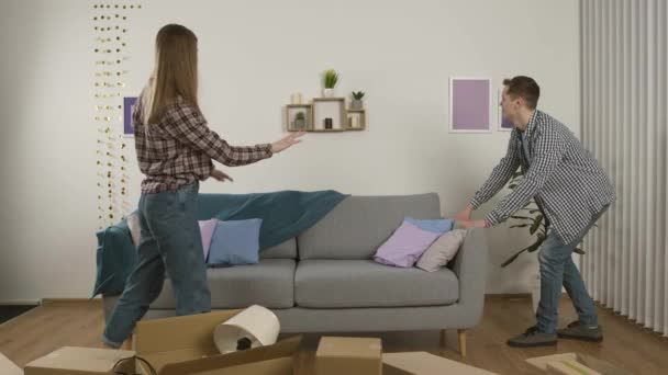 Lächelndes Paar bewegt Couch, zeigt Daumen hoch, umarmt und schaltet Fernseher ein