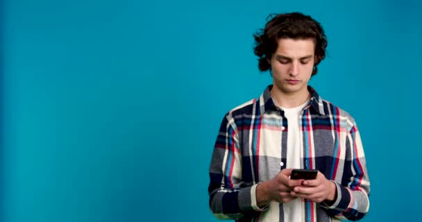 Young man using smartphone, looking away and shaking head isolated on blue background