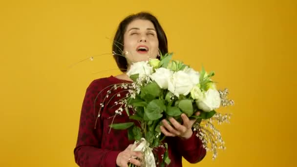 Happy middle aged woman sniffing flowers and smiling at camera