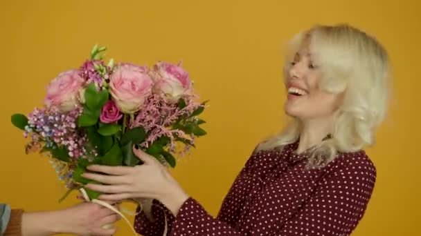 Happy blonde girl accepting flower bouquet and laughing at camera