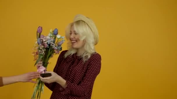 Blonde young woman using smartphone and accepting flowers with happy smile