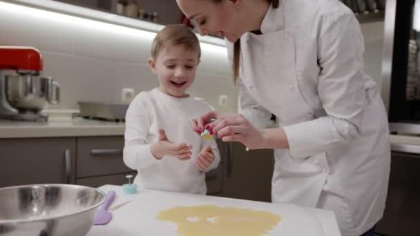 Glückliches Kind mit seiner glücklichen Mutter bereitet gemeinsam Osterplätzchen zu, bereitet sich auf den Urlaub vor, positive Emotionen