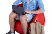 Nahaufnahme eines jungen Mannes in rotem Hocker mit Laptop