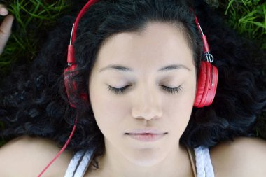 Young latin woman with headphones in a park.