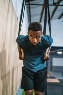 Portrait of young athletic man working out his muscles on rings at the gym. Crossfit, sport and healthy lifestyle concept.