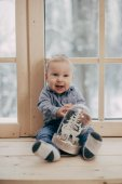Photo portrait of baby boy sitting with toy on wooden window sill