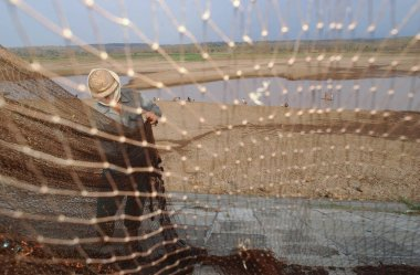 Madiun, Indonesia - August 28, 2003: A fisherman fixes his net near a drought stricken dam in Madiun, East Java Indonesia, on August 28th, 2003. The long drought season in Indonesia this year has left thousands suffering from access to water
