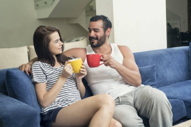 Beautiful young couple drinking coffee in the living room, Coupl
