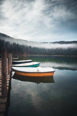 Beautiful sunrise on moody Lake Sfanta Ana with anchored boats against blue sky stock vector