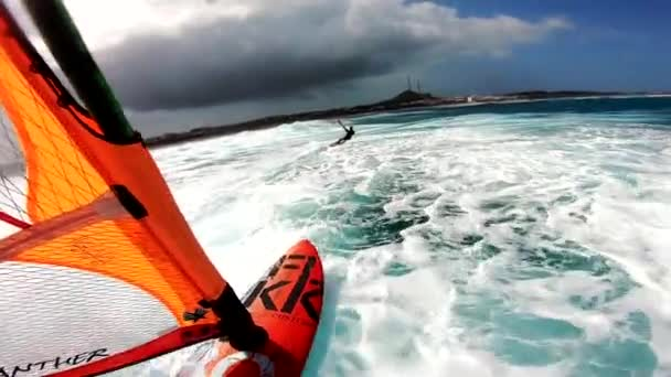 point of view of a windsurfer gliding along the turquoise surface of the sea and a jumping kitesurfer next to it. Windsurfing and kitesurfing together
