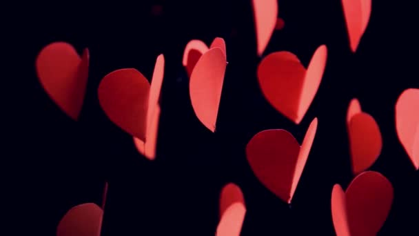 red paper hearts turning softly in 360 degrees with flashing red  lights bokeh in black background as love or valentine concept
