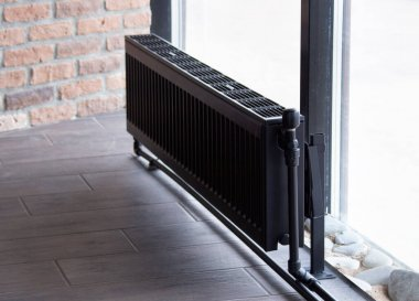 A black heating battery near the window in the winter heats the room, the house