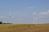 Landschaft Ansicht von riesigen Windkraftanlagen auf einem landwirtschaftlichen Feld Einstellung mit blauem Himmel Hintergrund, mit Kopierraum